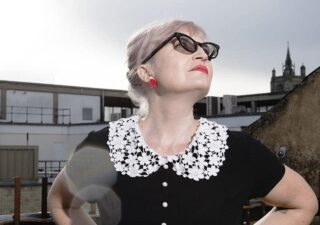 photo of Helen Ivory looking up at the sky wearing a black top with a little lacy white collar, red earrings, red lippy and black sunglasses, against buildings. Definitely a foxy rockabilly vibe going on here.