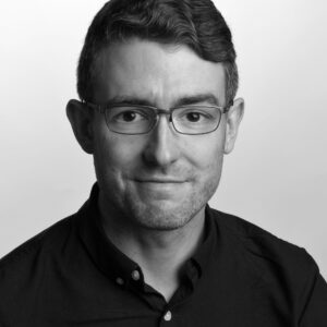 Black and white photo of Ben Wilkinson, a young friendly looking man with glasses