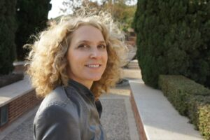 alice hiller with curly blonde hair wearing a grey jacket standing in a formal park
