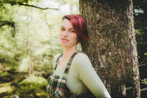 Kim Moore with red hair wearing a green top and green check dungarees leaning against a tree