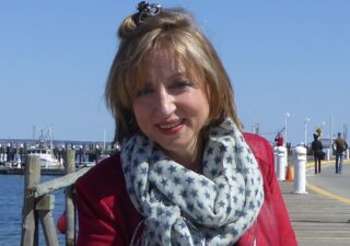 Anne-Marie Fyfe sitting on a wooden boardwalk in Massachusetts. Wearing a red jacket and a white scarf with dark blue stars around her neck.